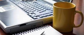 office coffee cups. coffee cup of canterbury on office desk beside a laptop and notepad in vernon cups e