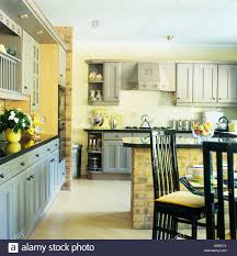 pale yellow dining room. stock photo tallback black chairs at table in yellow kitchen dining room with pale blue fitted units and laminated wood flooring