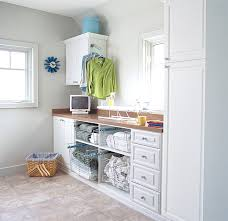 View in gallery Open shelving with pullout drawers in a crisp laundry room