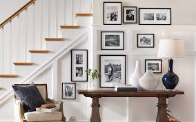 a wall art gallery of black and white photos on a staircase