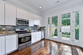 enticing white cabinets idea combined with gray subway glass backsplash and glossy wood floor