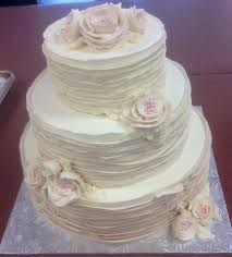 Tiered Rustic Wedding Cake With Buttercream Frosting And Flowers