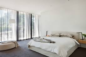 a modern bedroom with white walls and roof large window allows a lot of light