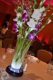 White Gladiolus, curly willow & purple dendrobium orchids make this  arrangement a stunning centerpiece.