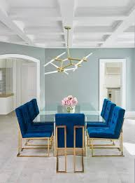 jonathan adler goldfinger blue velvet dining chairs frame a stunning long gl dining table with a br base featuring a curvy modern design