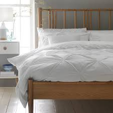 a spindle light oak double bed frame with white bedding