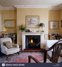 english country style living room with mantel piece arm chair and rug