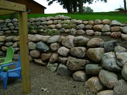 boulder retaining wall with patio and paver stair case