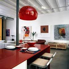 This contemporary kitchen mixes clean lines and neutral colors with the  bold red table and countertops.