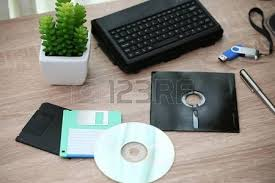 floppy office. old laptop and floppy disk desk with note a office