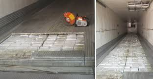 port officers rip open the floor of an empty semi trailer to find a