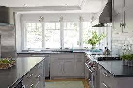 light gray wooden cabinets paired with black countertop in white kitchen