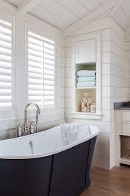 View in gallery Bathroom with shiplap walls and built-in storage shelving  near freestanding bathtub