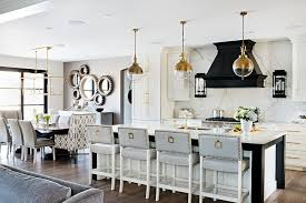 black and white kitchen island with gray upholstered barstools