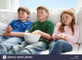 kids watching tv and eating. stock photo - three kids are sitting on the couch watching tv and eating popcorn \