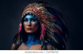 close up portrait of shamanic female with indian feather hat and colorful makeup native american