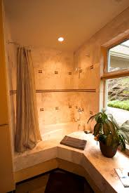 bathroom with travertine tile and jetted bathtub