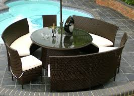 backyard swimming pool with parasol and round rattan dining set also white cushioning
