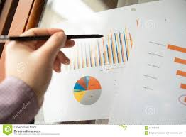 Male Hand Pointing At Charts Printed On A White Sheet Of