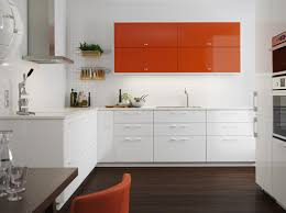 A medium sized kitchen with orange high-gloss doors combined with white  high-gloss