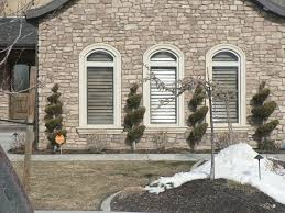 tremendous home exterior design with stone wall cladding and three arched windows with white