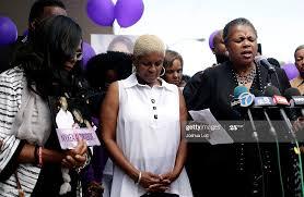 Diann Aldridge, center, the mother of Nykea Aldridge bows her head ...