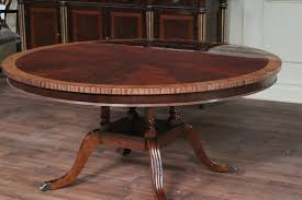 60 round flame mahogany dining table with satinwood banding and birdcage  pedestal base.
