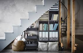 Stacked arrangement of IKEA storage boxes under a stairway.