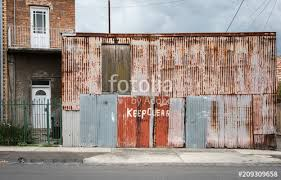 old and faded keep clear sign hand painted on a corrugated metal wall