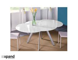 the erfly expandable round gl dining table extends its wings in metamorphosis to bee a full 8 seat dinner setting the