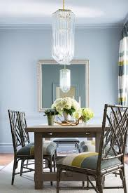 stunning blue and green dining room is illuminated by a long crystal chandelier hung from a pale blue ceiling over a gray wood dining table surrounded by