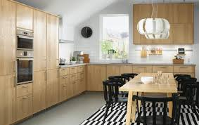 An oak kitchen with stainless steel appliances combined with black chairs  and an oak dining table