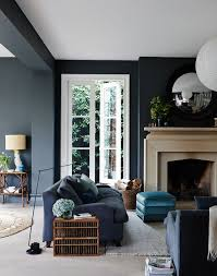 The pale stone of the fireplace looks so striking against the dark grey of  the walls in this traditional living room