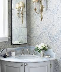 gorgeous blue and gray bathroom with gray corner bow front bathroom vanity paired with blue stone countertop and black rectangular bathroom mirror