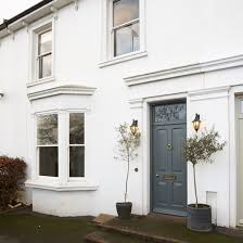 pretty white front door. On The Front Of Simple White Build Stands An Elegant, Ashen Grey Door  And Two Lean, Potted Trees Acting As Guards Pretty