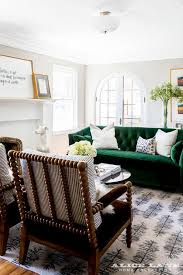 emerald green velvet tufted sofa with spindle chairs
