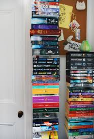 vertical bookshelves are just one of the clever storage ideas in this tiny teenage bedroom