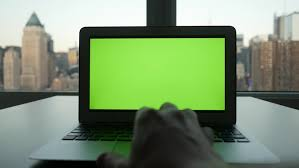 green office desk. laptop computer with isolated green screen background modern city office desk view working at n