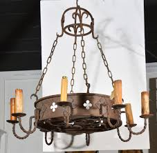 this antique french round iron chandelier has a tall metal band of rusted iron with eight