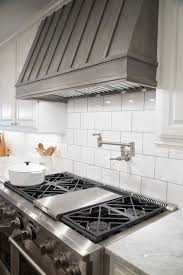 fixer upper gorgeous kitchen with crisp white cabinets paired with carrera marble countertops and large subway tiled backsplash flank stained wood hood