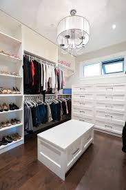 chic walk in closet features a white sheer drum pendant with crystal droplets hanging over a storage bench with drawers facing a built in dresser placed