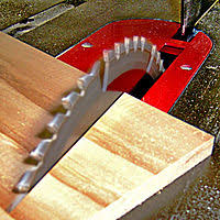 the blade of a table saw cutting into wood