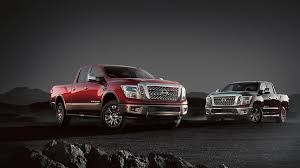 nissan trucks sitting in gravel with dark background