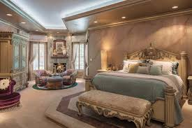 luxury master bedroom furniture. the master bedroom is a relaxing retreat with spacious sitting area and quartzite fireplace gold finishes on furniture complement soft metallic luxury