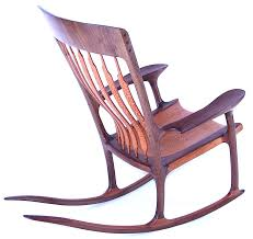 wooden rocking chair. the chair it self has a hand sculpted seat that is built with brazilian lace wood sandwiched between walnut, when carved exposed. wooden rocking