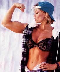 corinna everson tensing her bicep and revealing her shredded figure in front of what seems