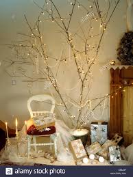 Home-made Christmas tree of fairy lights on tall branches above Christmas  presents