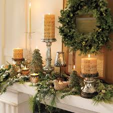 trendy fireplace and mantel decorated with pottery barn wreath and candle lights
