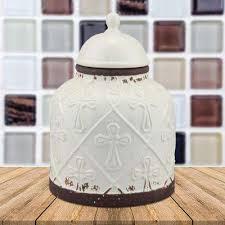 worn white ceramic cross cookie jar