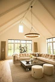 beautiful living room features a paneled cathedral ceiling accented with a ralph lauren roark modular chandelier illuminating a beige tufted slipcovered